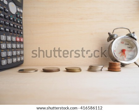 Coins tower, calculator and clock on wood background  - stock photo