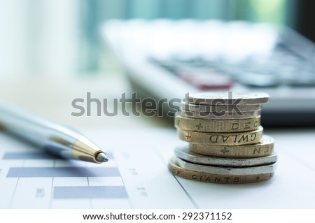 Coins with pen and blur calculator background - stock photo