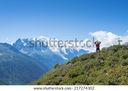 COL DE BALME, FRANCE - SEPTEMBER 01: Backpacker stretching and looking at view with Mont Blanc in the background. The area is a stage of the Mont Blanc tour. September 01, 2014 in Col de Balme. - stock photo
