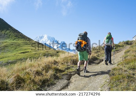 COL DE BALME, FRANCE - SEPTEMBER 01: Backpackers walking on trail with Mont Blanc in the background. The area is a stage of the popular Mont Blanc tour. September 01, 2014 in Col de Balme. - stock photo