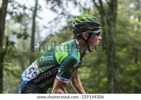 COL DU PLATZERWASEL,FRANCE - JUL 14: The French cyclist Thomas Voeckler (Team Europcar) climbing the road to mountain pass Platzerwasel, Vosges Mountains,during Le Tour de France on July 14 2014  - stock photo