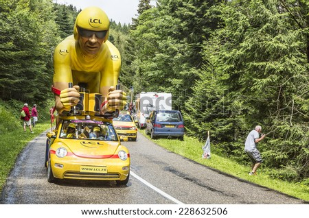 COL DU PLATZERWASEL,FRANCE - JUL 14: The LCL yellow mascot during the passing of the Publicity Caravan on the road to Mountain Pass Platzerwasel, during Le Tour de France on July 14 2014 - stock photo