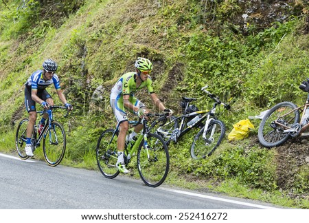 COL DU TOURMALET, FRANCE - JUL 24:The cyclists Alessandro De Marchi and Bartosz Huzarski climbing the difficult road to Col de Tourmalet in the stage 18 of Le Tour de France on July 24, 2014. - stock photo
