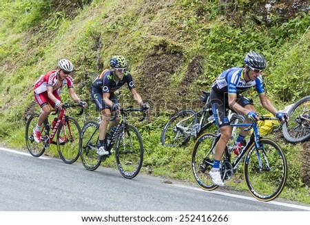 COL DU TOURMALET, FRANCE - JUL 24:The cyclists Bartosz Huzarski, Jon Izagirre Insausti and Yury Trofimov climbing the road to Col de Tourmalet in the stage 18 of Le Tour de France on July 24, 2014. - stock photo