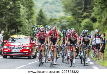 COL DU TOURMALET, FRANCE - JUL 24, 2014:Three cyclists from Lotto Belisol Team lead a part of the peloton on the road to Col de Tourmalet in the stage 18 of Le Tour de France on July 24, 2014. - stock photo