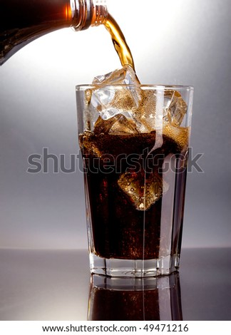 cola being poured in to a glass from a height - stock photo