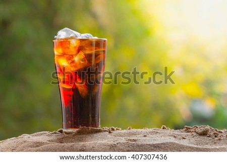 cola in glass with ice cubes on sand, nature background - stock photo