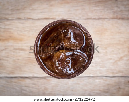 Cola in glass with ice from top view on wood. - stock photo