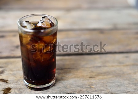 Cola in glass with ice on wood background - stock photo