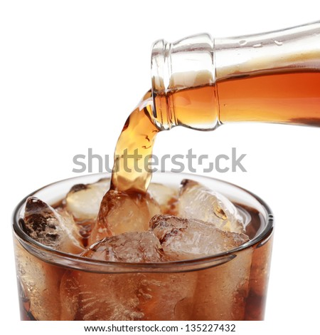 Cola is pouring from a bottle into a glass, isolated on white - stock photo