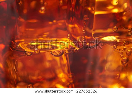 cola with ice cubes, blurred - stock photo