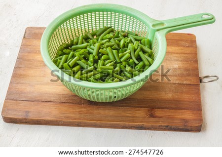 Colander with raw  green bean on the cutting board on the kitchen table - stock photo