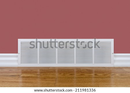 Cold air return grille on wall sitting on hardwood floor - stock photo