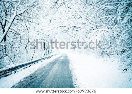 cold and snowy winter road through wood - stock photo