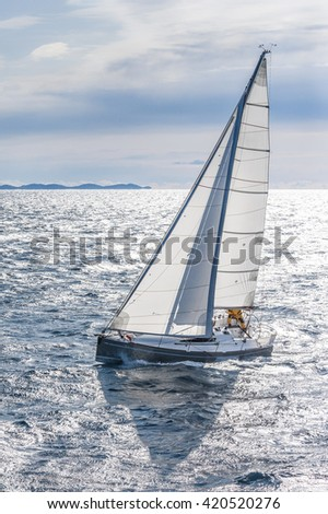 Cold and sunny day on the sea with sailing boat. White sails.