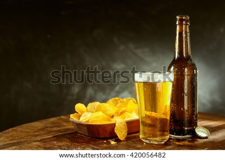 Cold beer in a long glass alongside an empty brown bottle and bowl of potato crisps on a bar counter with copy space - stock photo
