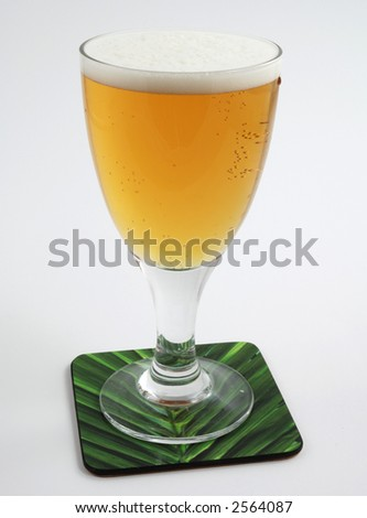 Cold beer on coaster - stock photo