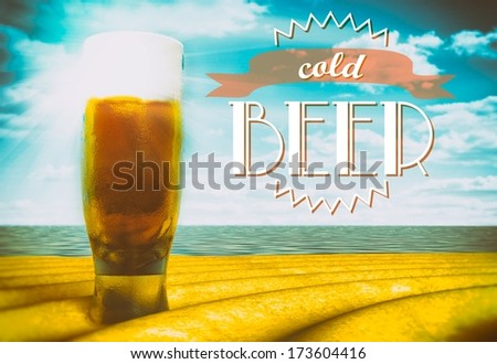 Cold beer sign with glass on beach - stock photo