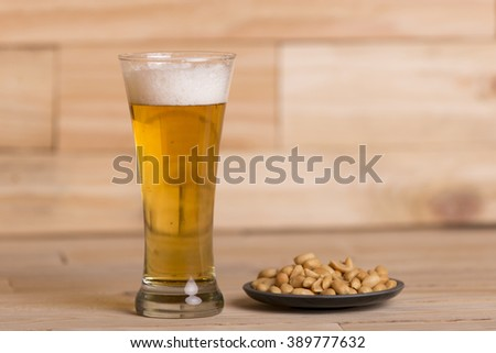 Cold beer with roasted peanuts, on wooden table, Still Life style - stock photo