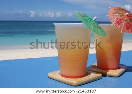 Cold beverages on coasters at beach front of island resort - stock photo