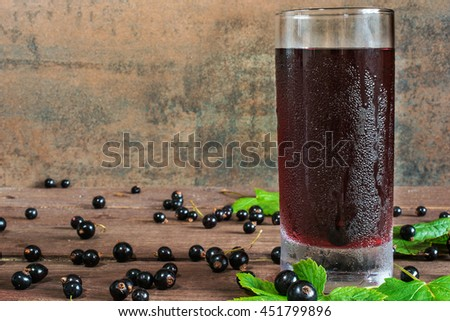 cold black currant juice in a glass on wooden table with ripe berries and green leaves around. cooling drink. close up - stock photo
