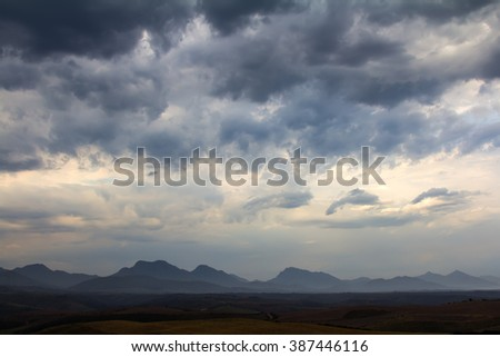 cold blue cloudscape with distant mountain peaks in the background and rolling fields in the foreground - stock photo