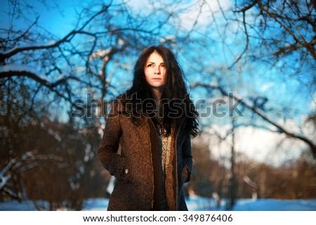 Cold blue outdoor portrait of pretty young woman in warm coat posing in winter O