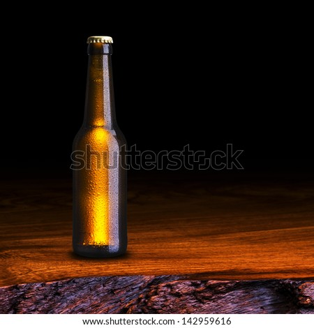 Cold Bottle of Beer on wood table - stock photo