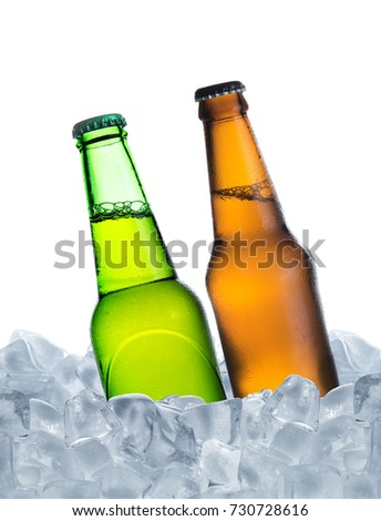 Cold bottle of beer with drops in ice cubes isolated on a white