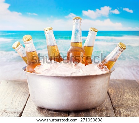 cold bottles of beer in bucket with ice over sea  - stock photo