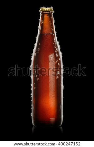 Cold brown bottle of beer with water droplets and ice over black background - stock photo