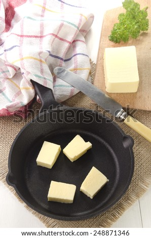 cold butter cubes in a cast iron pan - stock photo