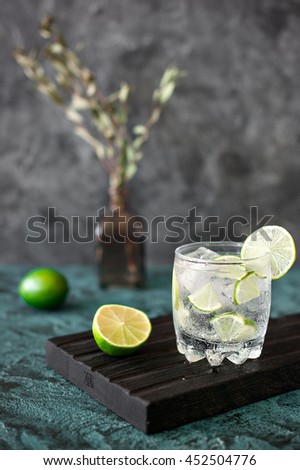 Cold cocktail with lime, tonic, vodka and ice on dark background - stock photo