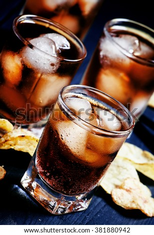Cold Cola with ice in glasses and potato chips on a dark background, unhealthy eating habits, selective focus