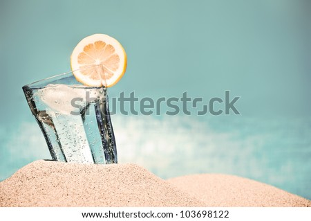 Cold drink with ice and a slice of lemon on the beach on a hot summer day - stock photo