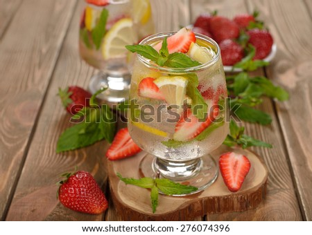 Cold drink with strawberries, lemon and mint on a brown background - stock photo