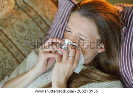 Cold flu illness of woman - tissue blowing runny nose - stock photo