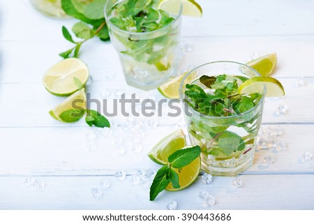 Cold fresh lemonade drink with slice of lime on the glass. Slices of lime and mint leaves on a  white wooden background - stock photo