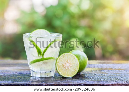 Cold fresh lemonade with lemon on wooden table. - stock photo