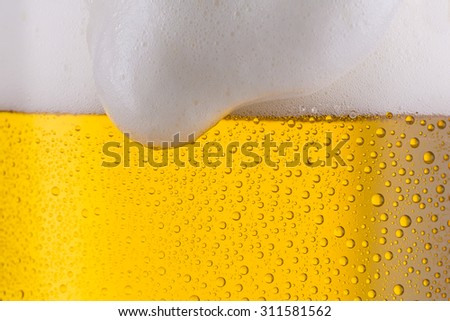 cold fresh overflowing beer with froth from Bavaria - stock photo