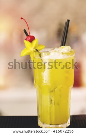 cold freshness summer cocktail with carambola at bar - stock photo