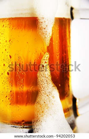 cold glass of beer with foam on a white background - stock photo