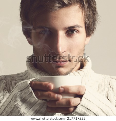 Cold. Handsome guy with cup of hot tea - stock photo