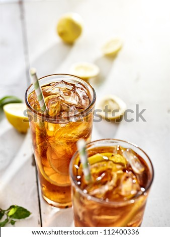 cold ice tea with sliced lemons and straws - stock photo