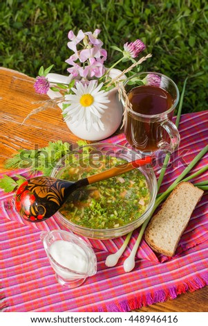 cold kvass soup with chopped vegetables and meat, wooden spoon, herbs, sauce, bread and kvas on the wooden table