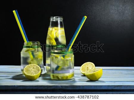 Cold lemonade in bottles with lemons on a black background - stock photo