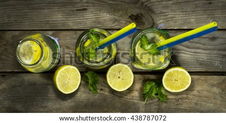 Cold lemonade in bottles with lemons on a wooden background. Top view - stock photo