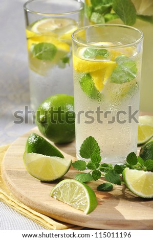 Cold lemonade in glass with ice, lime and lemon on cutting board - stock photo