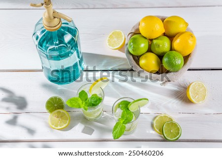 Cold lemonade with mint leaf in sunny garden - stock photo