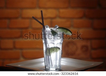 Cold limpid alcoholic cocktail with ice cubes and slices of lime in tall glass with two drinking straws standing on white square plate on brown brick wall background, horizontal photo - stock photo
